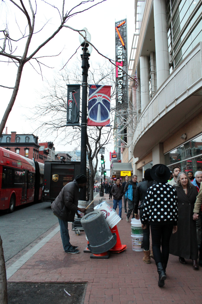 A street performer drums on buckets outside of the Verizon Center on Wednesday, March 25, 2015, in Washington, D.C.