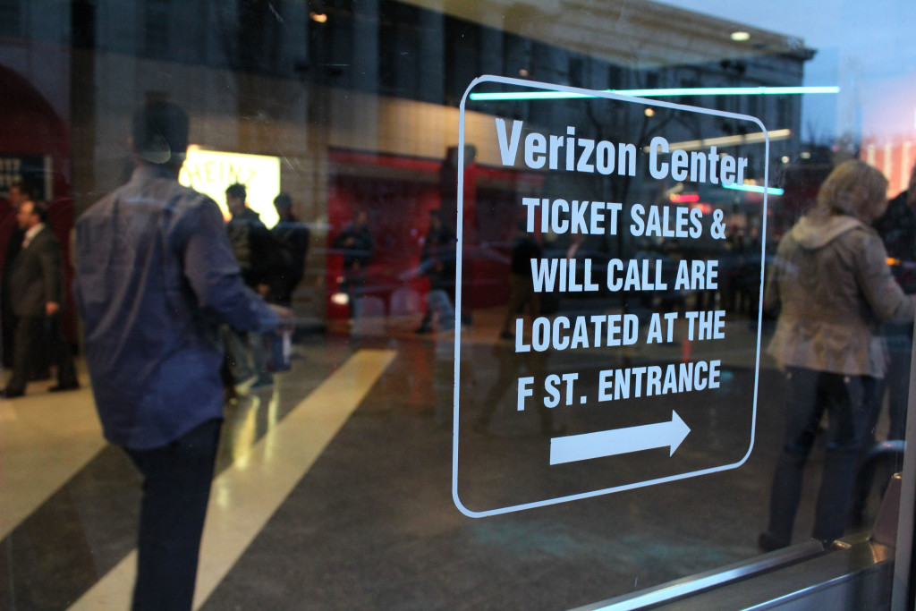 Patrons can be seen through a window of the Verizon Center in Washington, D.C., making their way to their seats with drinks and snacks ahead of a basketball game between the Washington Wizards and the Indiana Pacers.