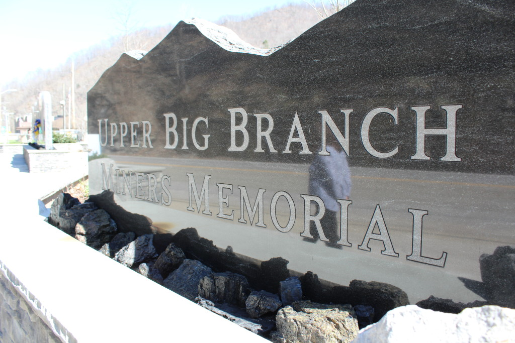 The reflection of a woman is seen in part of the memorial for the Upper Big Branch miners in Whitesville, W.Va.