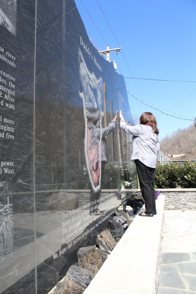Patty Lavender stands on the UBB memorial as she touches the name of Timmy Davis, her cousin that died in the disaster. Davis' name, along with the names of the 28 others who died, are etched on the memorial.