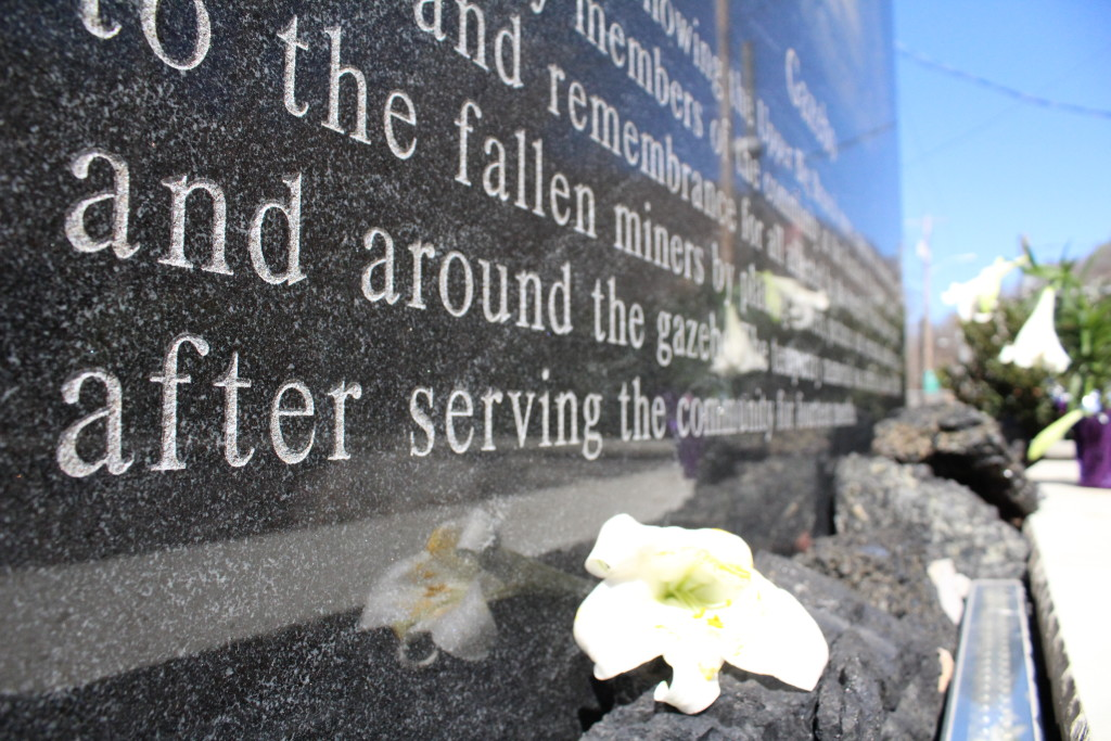 A flower rests on top of pieces of coal that sit at the base of the UBB memorial in Whitesville, W.Va.