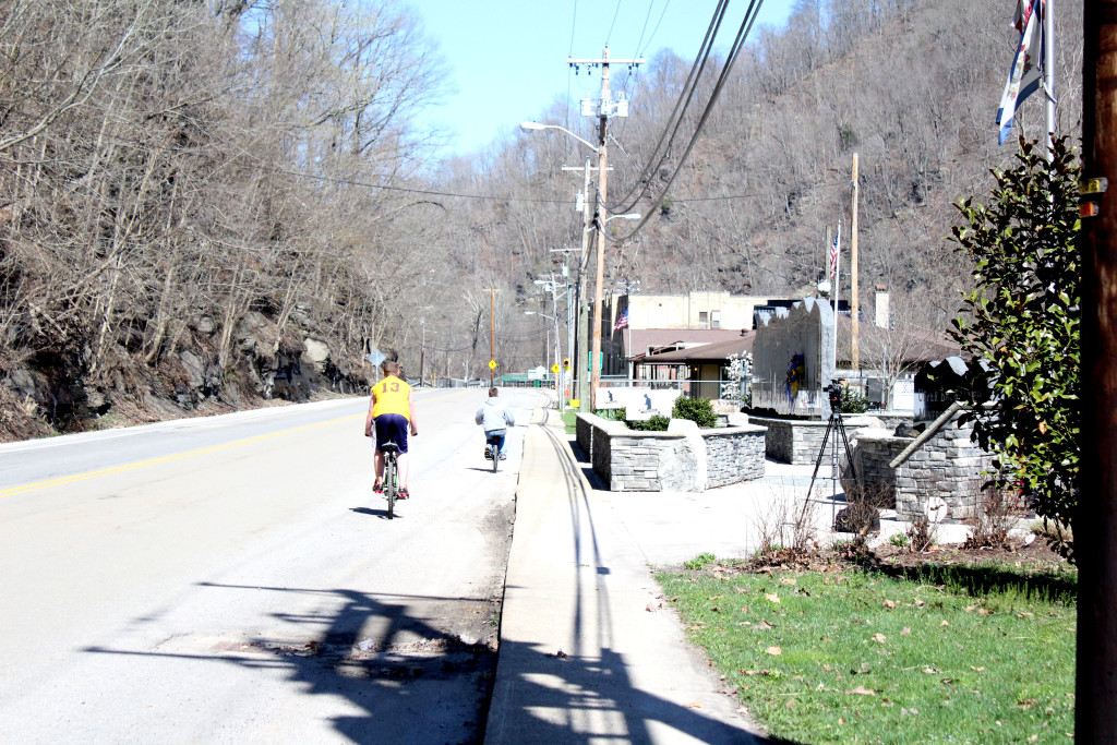 Two kids bike past the memorial on the fifth anniversary of the mine disaster, which fell on Easter Sunday.