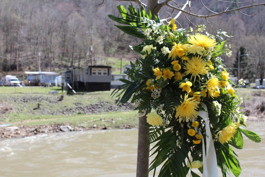 A wreath of flowers sits near the UBB memorial in Whitesville, W.Va. A trailer park can be seen in the background, across the river from the memorial.